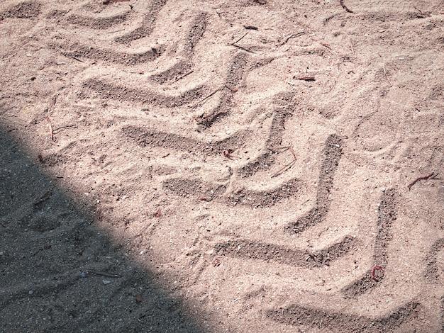 Volledige frame achtergrond van de afdruk van de tractorband in het zand