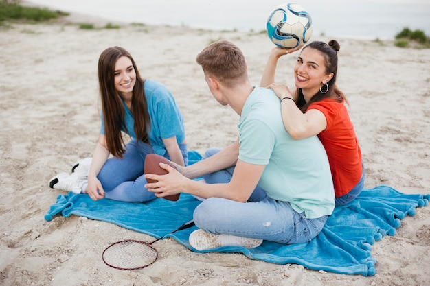 Volledige geschoten gelukkige vrienden die op het strand zitten