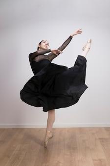 Volledige geschotene ballerina die binnen presteert