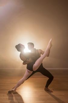 Volledige geschotene ballerina die door mannelijke danser wordt gehouden