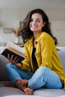 Volledige geschotene gelukkige vrouw die een boek houdt
