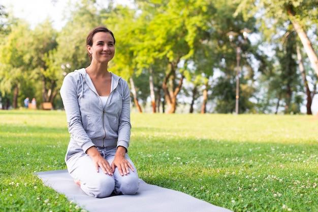 Volledige geschotene smileyvrouw op yogamat