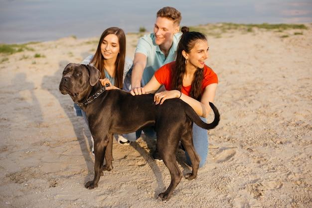 Volledige geschotene vrienden met hond op het strand