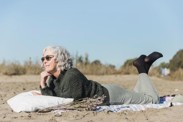 Volledige geschotene vrouw die op het strand legt