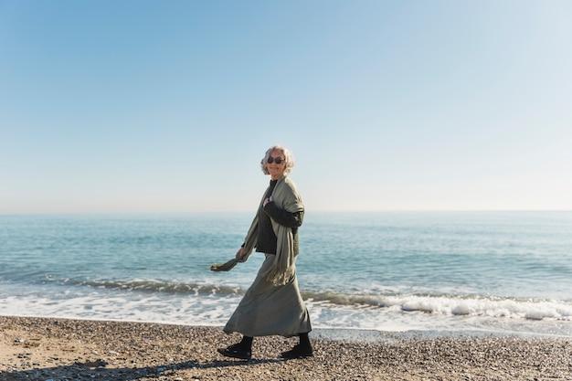 Volledige geschotene vrouw die op het strand loopt