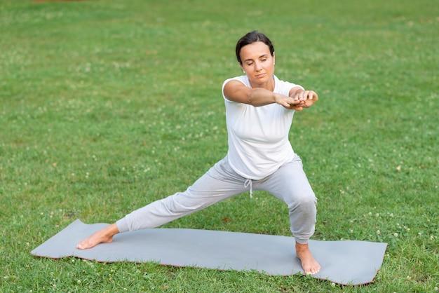 Volledige geschotene vrouw die yoga in aard doet