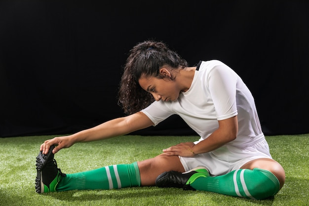 Volledige geschotene vrouw in zich sportkleding het uitrekken