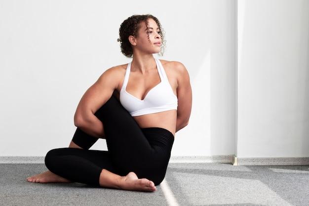 Volledige geschotene vrouw met spieren die op de vloer zitten