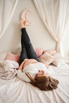 Volledige geschotene zwangere vrouw die in bed legt