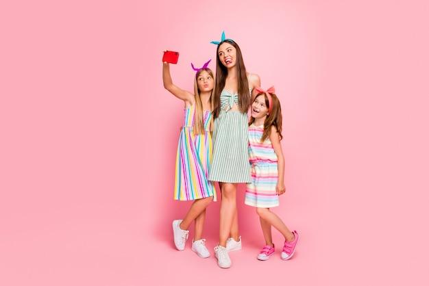 Volledige grootte foto van een vrouw en twee schoolkinderen met lang blond brunette kapsel sturen luchtkusjes waardoor selfie rok hoofdbanden geïsoleerde roze achtergrond dragen