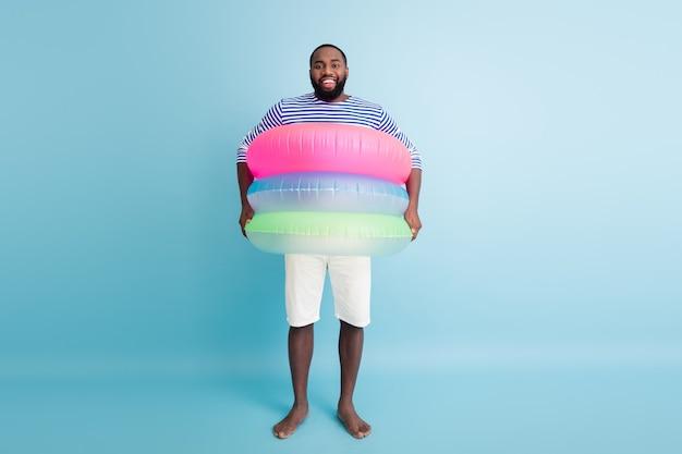 Volledige grootte foto van funky grappige barefoot afro amerikaanse kerel geniet weekend hebben kleurrijke ring vlotter redder in nood boei klaar zwemmen in oceaan dragen witte korte broek japon geïsoleerde blauwe kleur muur