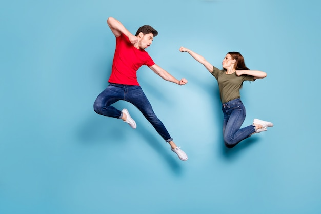 Volledige grootte foto van gekke man twee mensen vrouw man echtgenoten oneens spring gevecht kickboksen dragen groen rood t-shirt denim jeans sneakers geïsoleerd op blauwe kleur achtergrond