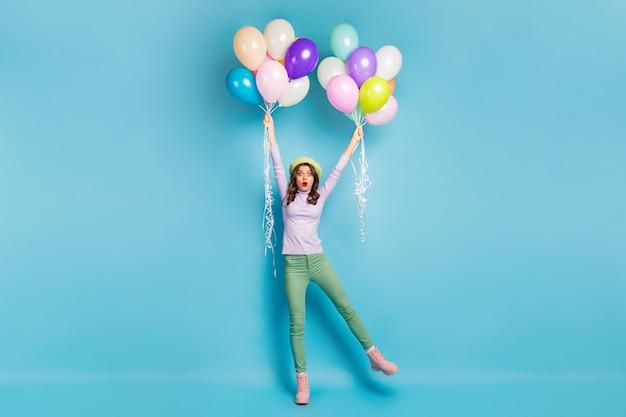 Volledige grootte foto van gekke mooie dame houdt veel lucht ballonnen armen omhoog wind waait dragen paarse trui baret pet groene broek laarzen geïsoleerde blauwe kleur muur