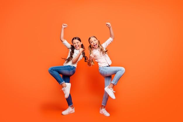 Volledige grootte foto van opgetogen uitdrukking gekke funky twee vriendinnen vieren wedstrijd winnen schreeuwen ja, vuisten heffen dragen casual stijl outfit geïsoleerde oranje kleur achtergrond