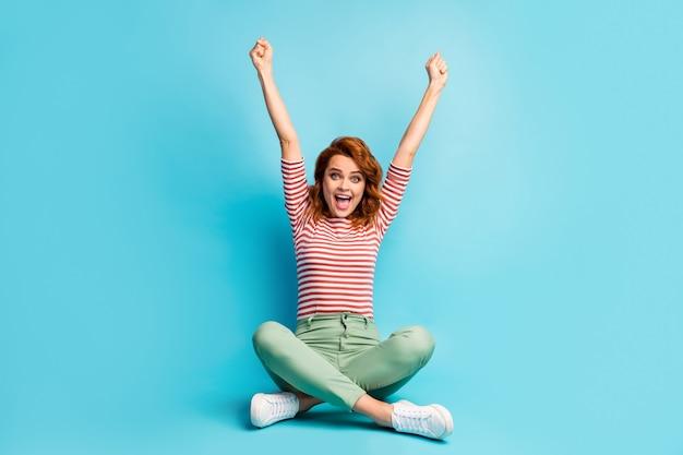 Volledige grootte foto van opgetogen vrouw zitten gekruiste benen winnen fortuin loterij vuisten heffen schreeuwen ja draag trendy sneakers geïsoleerd over blauwe kleur