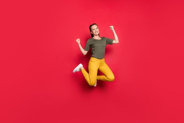 Volledige grootte foto van opgewonden duizendjarige dame springen hoge vrolijke stemming ondersteunende favoriete voetbalteam dragen casual gele broek groen t-shirt geïsoleerde rode kleur achtergrond