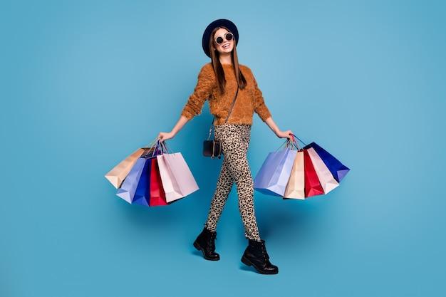 Volledige grootte foto van positieve emoties meisje toerist winkelen weekend houden veel tassen zien er goed uit dragen herfst herfst winter bruine trui broek koppeling geïsoleerde blauwe kleur muur
