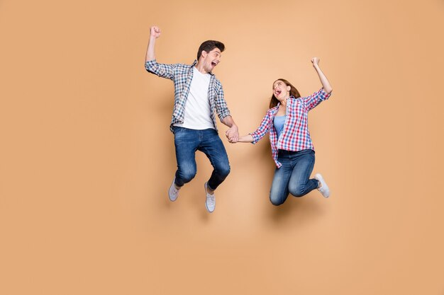 Volledige grootte foto van twee mensen gekke dame kerel springen hoog vieren beste overwinning verhogen vuisten verkoop winkelen hand in hand dragen casual plaid jeans kleding geïsoleerde beige achtergrond