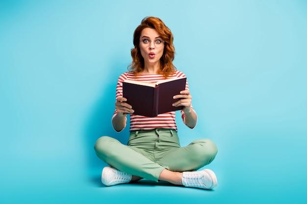 Volledige grootte foto van verbaasde vrouw zitten benen gekruist boek lezen ongelooflijk fictieverhaal onder de indruk schreeuw wow omg draag groen witte kleding geïsoleerd over blauwe kleur