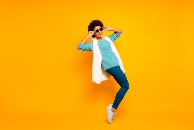 Volledige grootte foto van vrolijk afro-amerikaans meisje voelt gek dansdanseres op nachtclub clubber touch zonnebril dragen blauw wit wintertaling pullover broek geïsoleerde gele kleur muur
