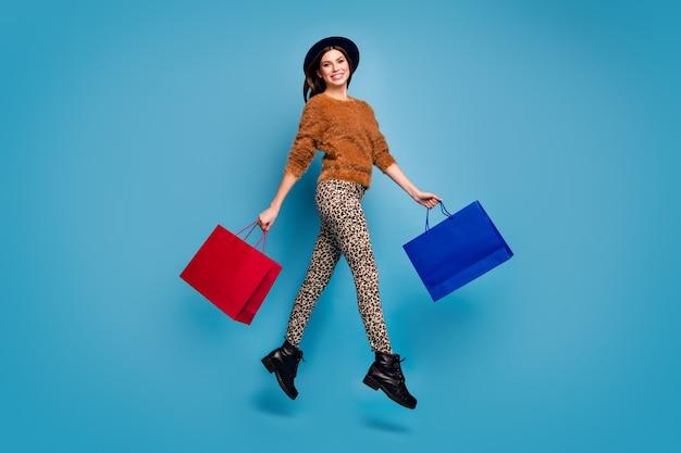 Volledige grootte foto van vrolijk meisje springen lopen houden off-sales koopje tassen genieten herfst lente reis dragen bruine casual trui broek retro vintage hoofddeksels laarzen geïsoleerde blauwe kleur muur
