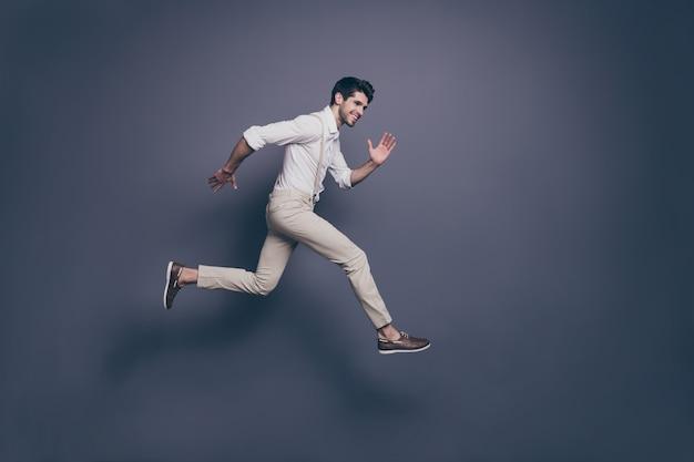 Volledige grootte profiel kant portret van vrolijke kerel sprong rennen na luxe zwarte vrijdag koopje veel plezier moderne kleding dragen.
