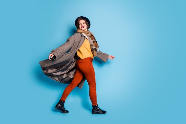 Volledige grootte profiel portret van grappige trendy reiziger dame straat lopen in het buitenland goed humeur wind waait dragen casual lange grijze jas sjaal broek hoed schoenen.