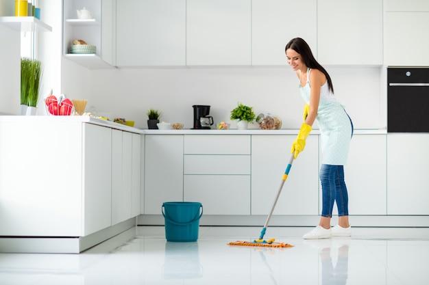 Volledige grootte profielfoto van positieve vrolijke meisje met dweil wassen vloer dragen witte singlet gele rubberen handschoenen gestippelde schort viel inhoud genieten van huishoudelijke taken in keuken huis binnenshuis