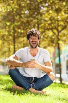 Volledige het lichaam het lachen mensenzitting in gras die aan muziek luisteren