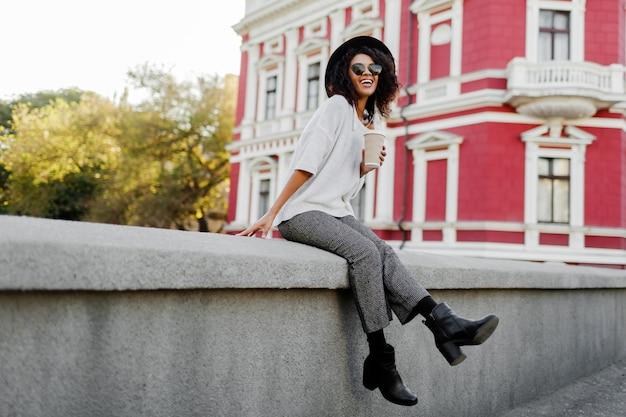 Volledige hoogte afbeelding van speelse zwarte vrouw met afro haren zittend op de brug en plezier maken.