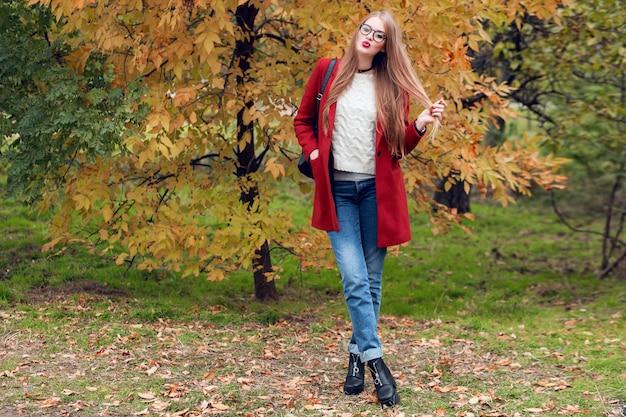 Volledige hoogte herfst mode beeld van mooie vrouw in rode stijlvolle jas en gebreide muts, rode lippen poseren op geel park.