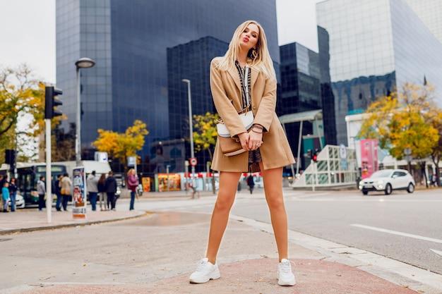 Volledige hoogte portret van vrij blonde vrouw poseren over stedelijke straat. beige jas en witte sneakers dragen. trendy accessoires. zorgeloze dame die langs de straat loopt.