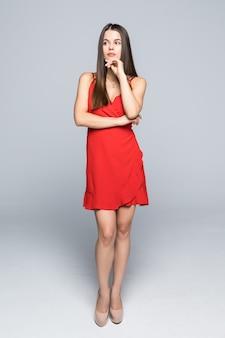 Volledige hoogte van aantrekkelijke maniervrouw die een slanke rode kleding draagt die op muur loopt.