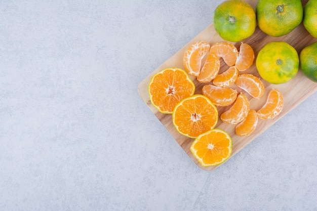 Volledige houten snijplank van zure mandarijnen op witte achtergrond. hoge kwaliteit foto