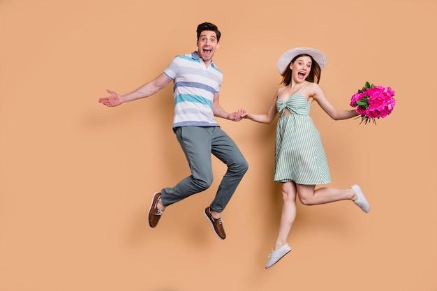 Volledige lengte aantrekkelijke dame man opgewonden paar sprong houden bos bloemen