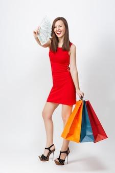 Volledige lengte aantrekkelijke glamour modieuze jonge vrouw in rode jurk met contant geld dollars, multi gekleurde pakketten met aankopen na het winkelen geïsoleerd op een witte achtergrond. ruimte voor advertentie kopiëren