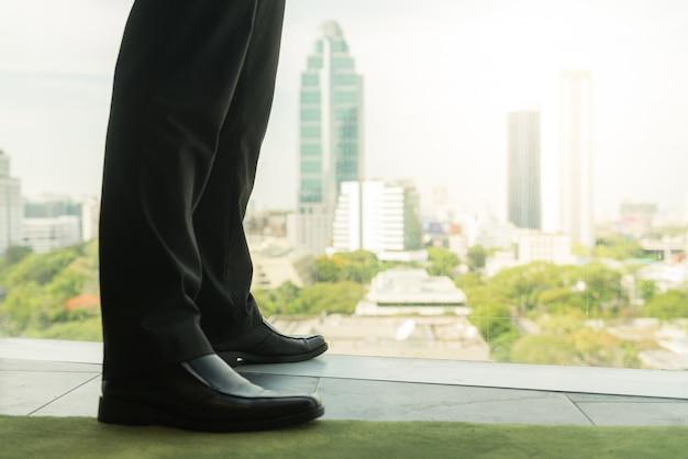 Volledige lengte achteraanzicht van succesvolle zakenman in kostuum staande in kantoor met handen op zijn middel, ceo kijkt door het raam in grote stad gebouwen, planning nieuw project, wachten op de vergadering om te beginnen