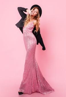 Volledige lengte afbeelding van sierlijke sexy blonde vrouw in maxi jurk met lovertjes en stijlvolle zwarte hoed poseren op roze muur. geweldig figuur. hoogte hakken. boodschappen doen. modieuze look.