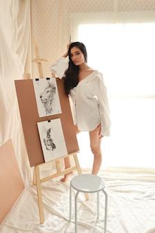 Volledige lengte asisn vrouw kunstenaar in wit shirt denken iets tijdens het tekenen foto met potlood (vrouw levensstijl concept)