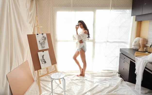 Volledige lengte aziatische vrouw kunstenaar in wit shirt koffie drinken tijdens het tekenen foto met potlood (vrouw levensstijl concept)