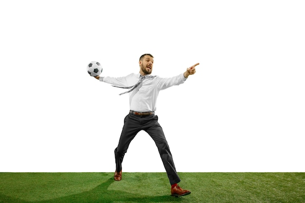 Volledige lengte die van een jonge zakenman speelvoetbal is ontsproten die op witte achtergrond wordt geïsoleerd.