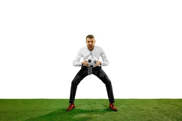 Volledige lengte die van een jonge zakenman speelvoetbal is ontsproten die op witte muur wordt geïsoleerd