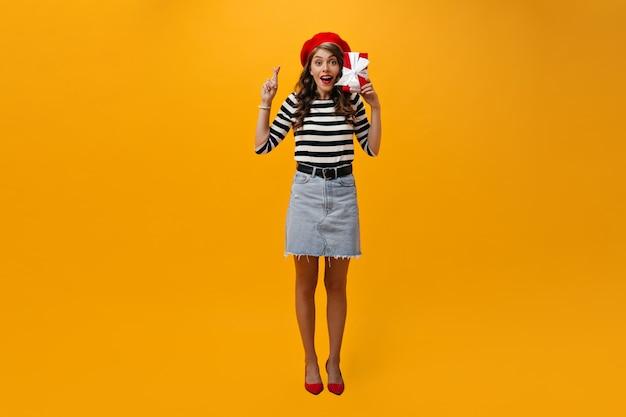 Volledige lengte die van vrouw is ontsproten die vingers kruist en rode giftdoos houdt. gelukkig meisje dat in rode baret en gestreept overhemd camera onderzoekt.