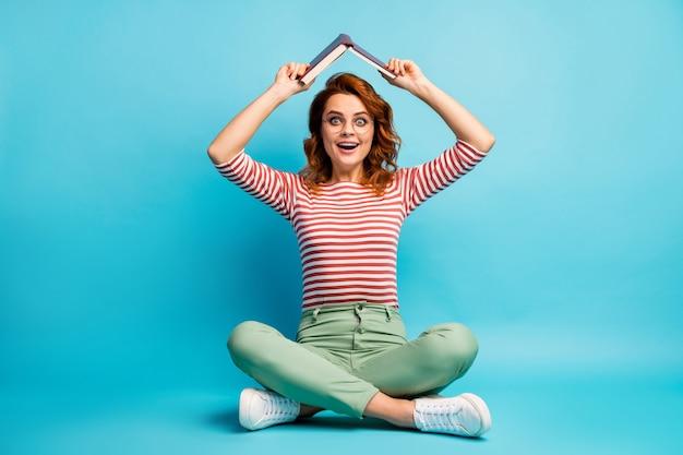 Volledige lengte foto gek verbaasd meisje zitten vloer benen gekruist willen rust ontspannen zet papierboek boven het hoofd onder de indruk schreeuw wow dragen witte groene broek broek schoenen geïsoleerde blauwe kleur