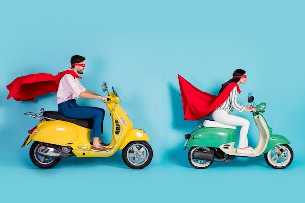 Volledige lengte foto van coole dame man rijden zitten twee vintage bromfiets dragen rode cape masker haasten weg halloween party spelen superhelden rol jas vliegen lucht geïsoleerde blauwe kleur muur