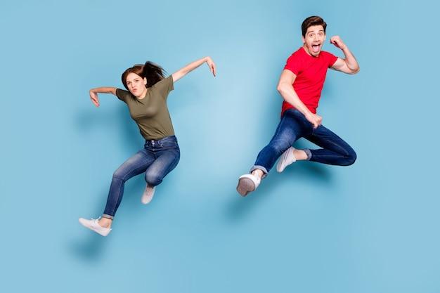 Volledige lengte foto van funky grappige gekke twee mensen studenten sportieve team man vrouw springen praktijk vechten sport oefening kick handen dragen casual stijl outfit geïsoleerde blauwe kleur achtergrond