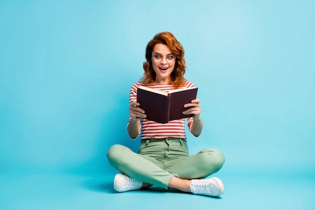 Volledige lengte foto van gekke boekenwurm vrouw zitten vloer rust ontspannen kruis benen lezen boek onder de indruk schreeuw wow omg draag wit groen schoeisel broek geïsoleerde blauwe kleur