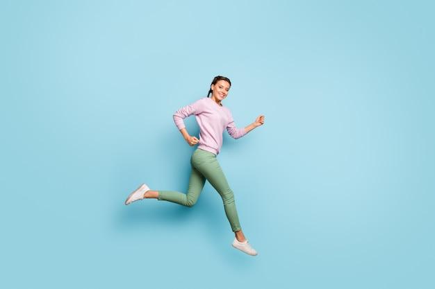 Volledige lengte foto van mooie dame hoog springen haasten winkelcentrum snelheid race laatste seizoen lage prijzen dragen casual roze trui groene broek geïsoleerde blauwe kleur