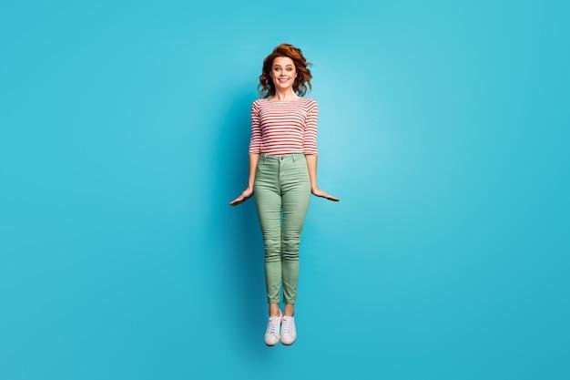 Volledige lengte foto van mooie dame hoog springen verheugend weekend mooi weer zonnige dag dragen casual rood wit overhemd groene broek schoeisel geïsoleerde blauwe kleur