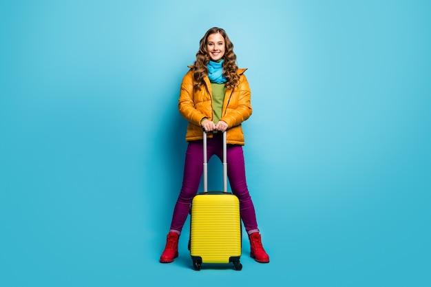 Volledige lengte foto van mooie dame reiziger in het buitenland houden rollende tas koffer luchthaven registratie vlucht dragen gele overjas blauwe sjaal broek schoenen geïsoleerde blauwe kleur muur
